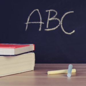 A photo of chalk, books and a blackboard