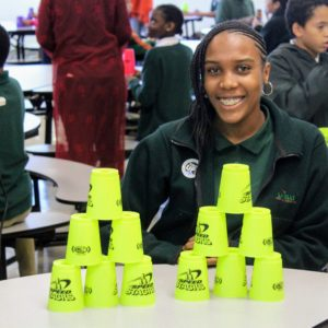 A student smiling for a photo with cups